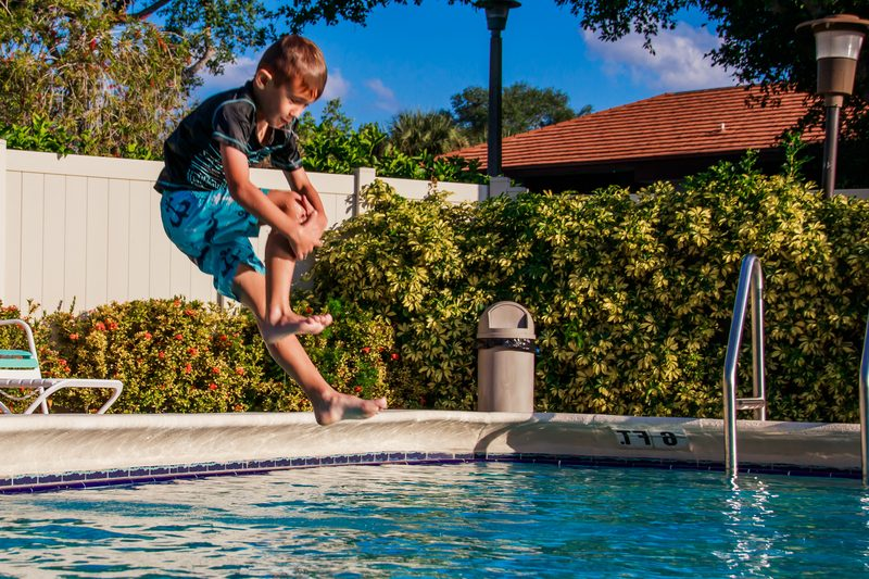 Young boy doing a cannonball into a pool.