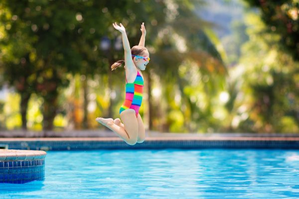 Young girl jumping into pool.