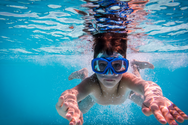 Young bot under water wearing face goggles.