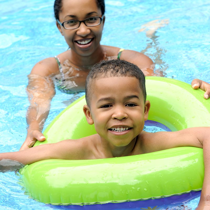 Mother and son in pool. The son has a green ring floatation device.